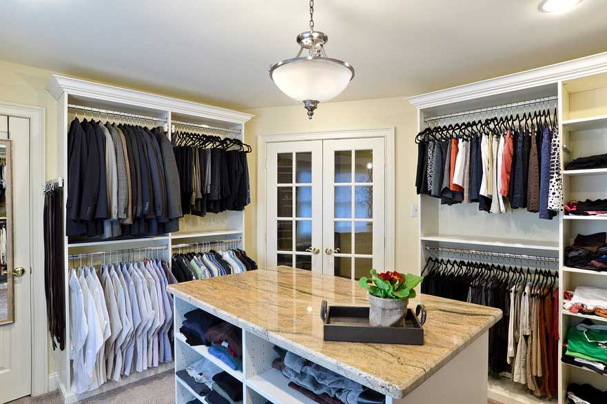 His and her closet with clothes neatly hung on hangers on both sides and organized