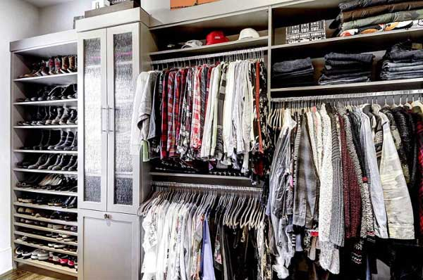 Walk-in closet neatly organized with clothing hung and folded