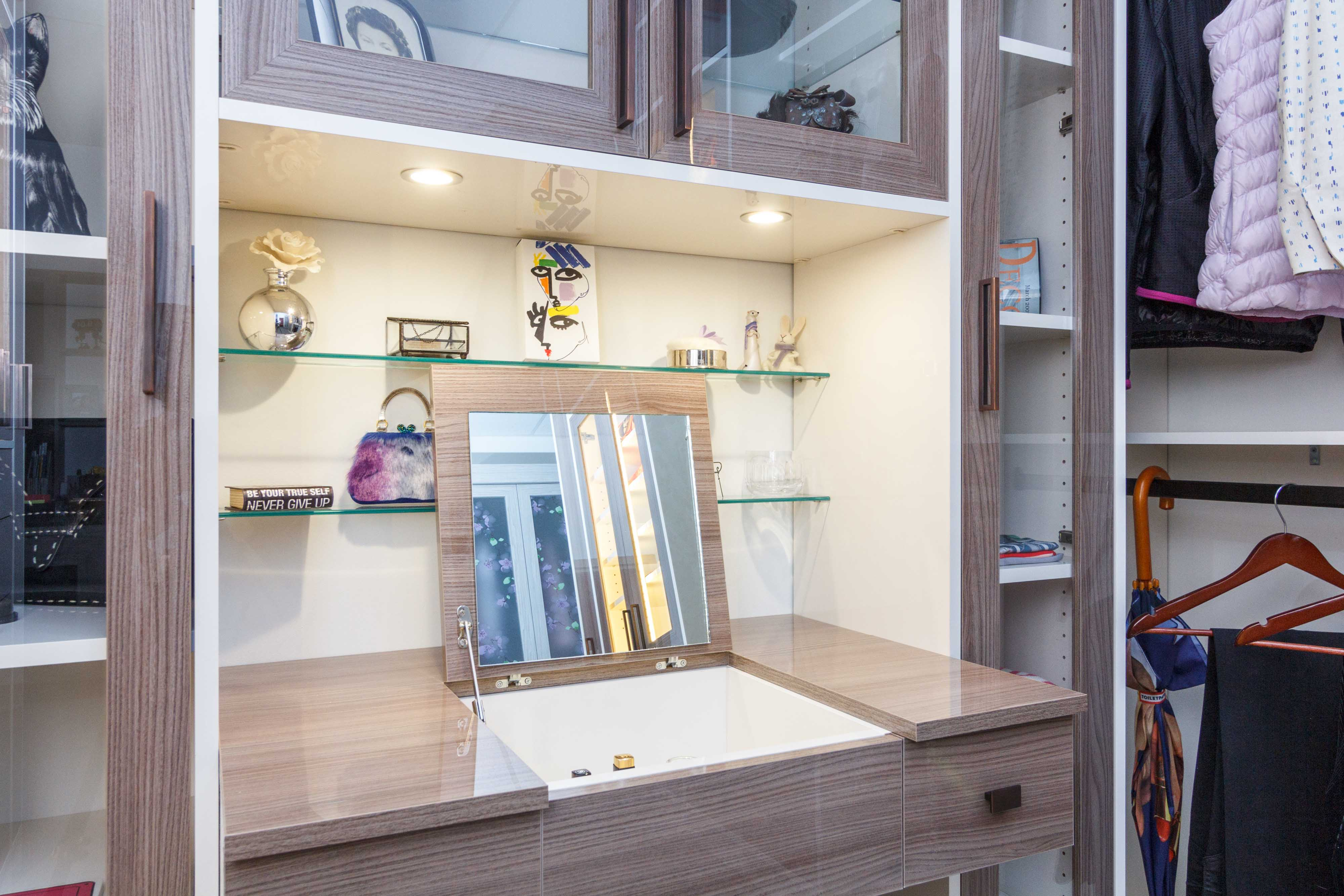 Trending Walk-in closet showcasing glass shelves and a flip up vanity